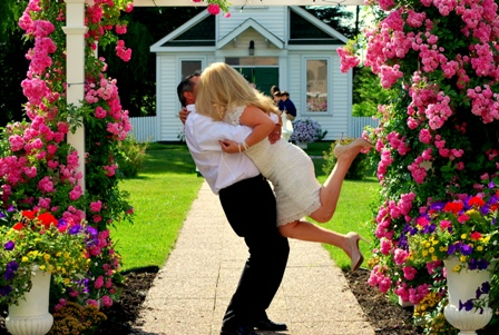 Blissful newly married couple kissing in front of The White Wedding Chapel at The Peninsula Inn, Niagara Falls, Ontario